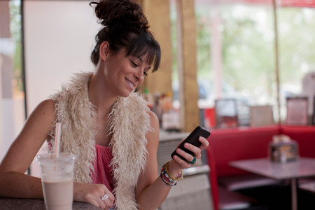 Young woman looking at mobile phone in diner