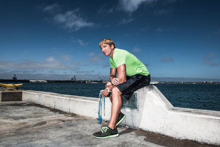 Young man in sportswear resting on pier