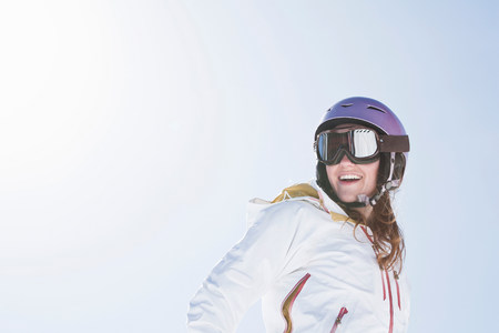 Young woman wearing ski goggles and helmet LANG_EVOIMAGES