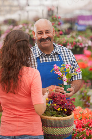 one mature woman only: Mature man serving young woman in garden centre,portrait