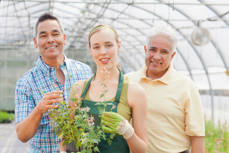 Senior,mature man and mid adult woman in garden centre,portrait