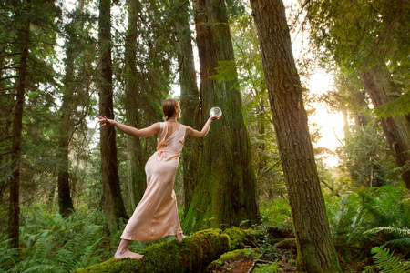 Mature woman standing on log in forest LANG_EVOIMAGES