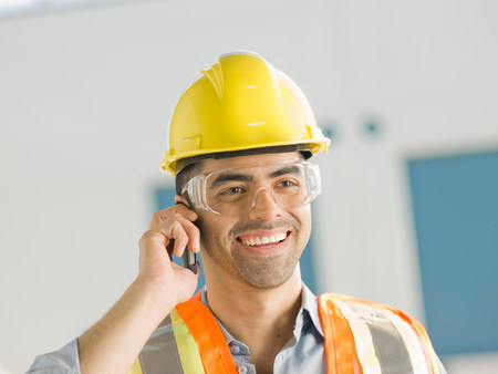 Mid adult construction worker using mobile phone,smiling LANG_EVOIMAGES