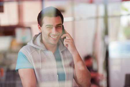 Young man using mobile phone in window of diner,smiling
