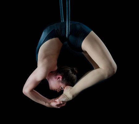exerting: Aerialist performing on hoop in front of black background LANG_EVOIMAGES