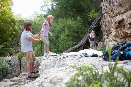 Young group of people setting up tent on rocks