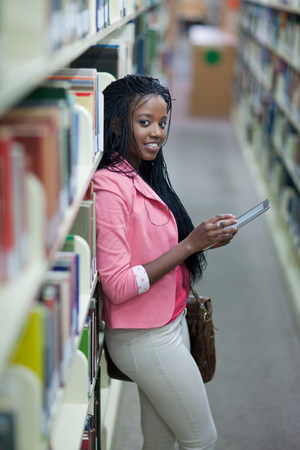 Female student using digital tablet in library LANG_EVOIMAGES