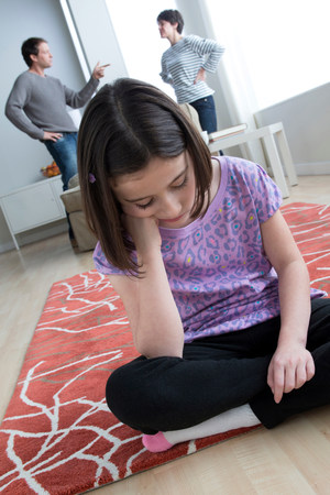 floor covering: Girl sitting on floor with parents arguing in background LANG_EVOIMAGES