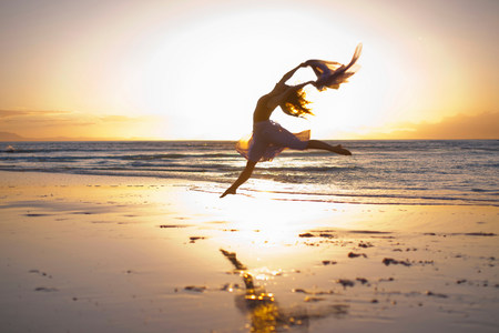Young woman dancing on sunlit beach LANG_EVOIMAGES