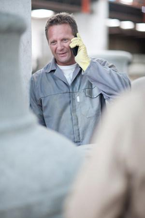 Factory worker talking on cellular phone LANG_EVOIMAGES