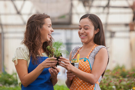 Young women holding plant in garden centre,smiling