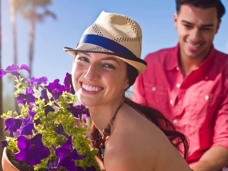 purples: Young woman wearing sun hat and holding purple flowers,portrait