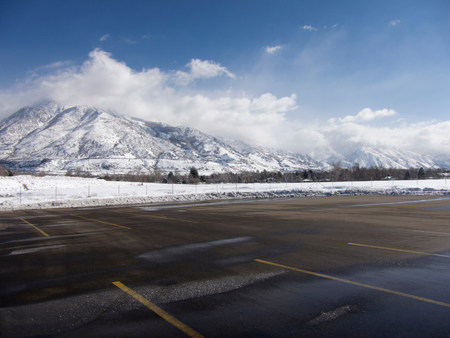 frozen lake: Empty parking lot with snow covered Wasatch Mountains in background,Salt Lake City,Utah,USA