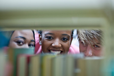 Three students peering through books