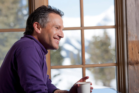 purples: Mature man holding hot drink indoors,smiling