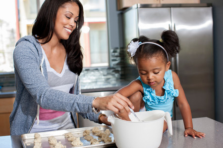 3 year old: Mid adult woman baking with daughter in kitchen LANG_EVOIMAGES