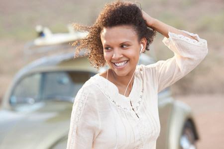 Young woman wearing earphones in desert on road trip,smiling