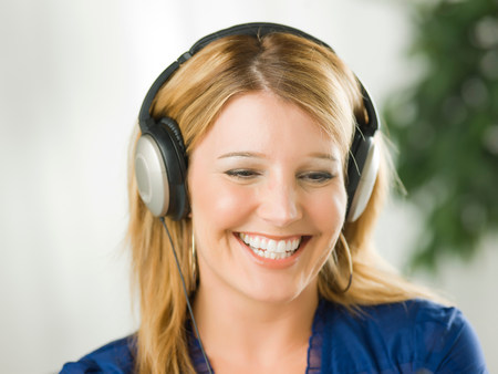 Mid adult woman wearing headphones and smiling