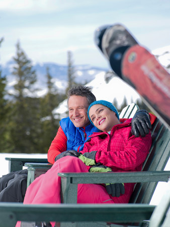 Mature man and young woman relaxing together in ski resort LANG_EVOIMAGES