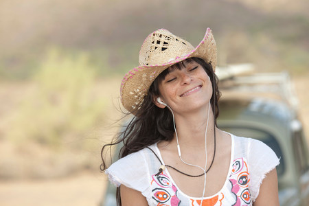 Young woman in cowboy hat wearing earphones,smiling
