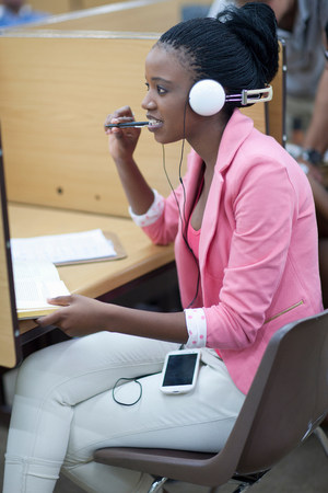 engrossed: Female student working in library with headphones