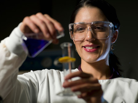 Young scientist in safety glasses mixing chemicals,smiling LANG_EVOIMAGES