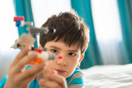 Boy playing with toy in bedroom LANG_EVOIMAGES