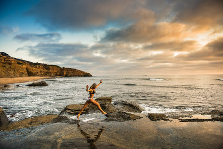 travel features: Young woman in bikini leaping from rocks on beach