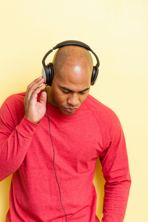 afro caribbean ethnicity: Portrait of mid adult male eyes closed with headphones