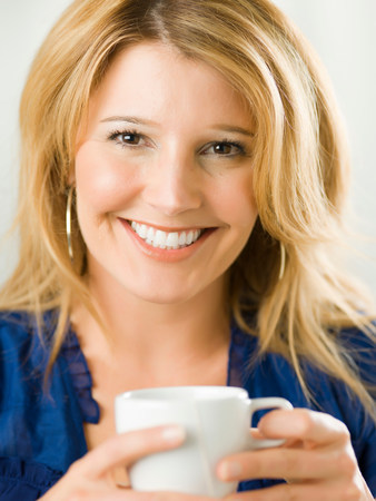 Mid adult woman holding cup and smiling,portrait