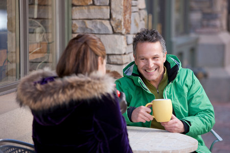 Mature man and woman enjoying drink in pavement cafe