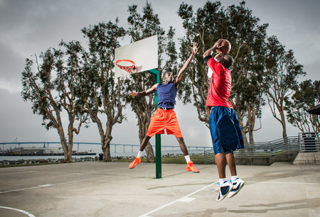exerting: Young basketball players jumping to score hoop LANG_EVOIMAGES