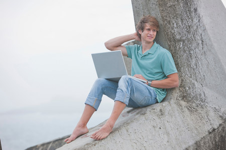 Young man using laptop on pier