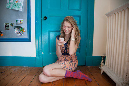 chillout: Teenager sitting in front of blue door,using mobile telephone