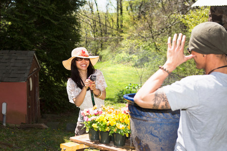 hosepipe: Woman spraying man with hosepipe
