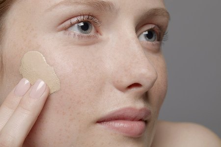 snug: Close up of part of young womans face,applying concealer LANG_EVOIMAGES