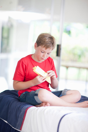 Boy on bed playing with paper aeroplane