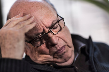 inconvenient: Senior man with eyes closed,wearing glasses,looking stressed