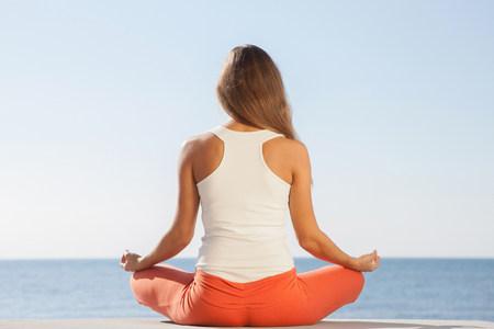 Mujer joven meditando por la vista trasera del mar