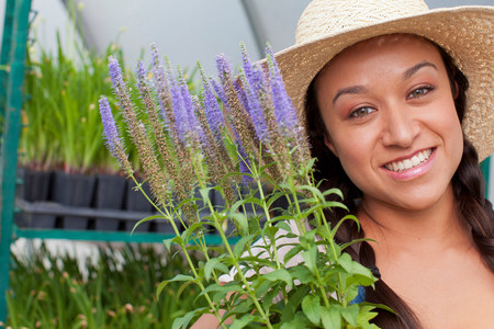 Young woman holding flowers in garden centre,portrait LANG_EVOIMAGES