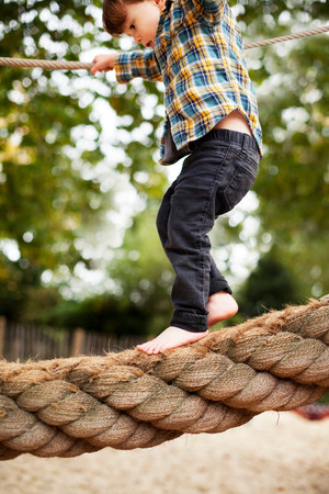 level playing field: Male toddler crossing rope bridge