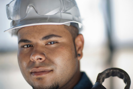housebuilding: Young construction worker wearing hard hat and holding wrench,smiling