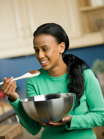 unhealthiness: Young woman holding mixing bowl and spoon,smiling