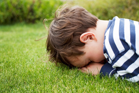 Male toddler hiding face down on grass LANG_EVOIMAGES