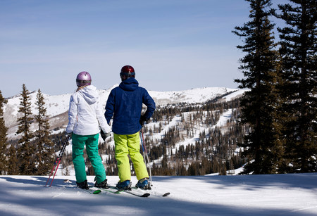 Young couple holding hands at top of ski run