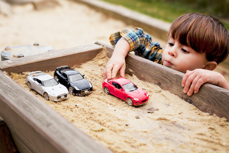 Male toddler reaching to play with toy cars in sandpit LANG_EVOIMAGES