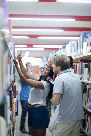 further: Students choosing books in library