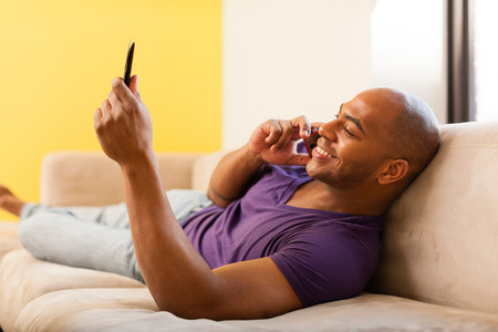 Mid adult male on sofa using digital tablet and mobile phone LANG_EVOIMAGES