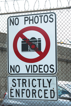 enforcing: No photography sign on wire fence