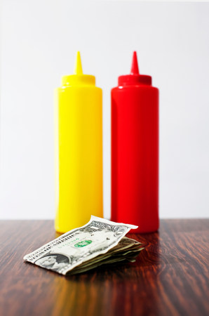 gratuity: Money on table next to mustard and tomato sauce